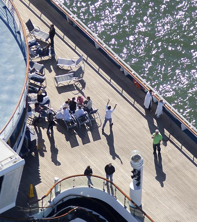 Passengers congregate on an upper deck of the disabled Carnival Lines cruise ship Triumph as it is towed to harbor off Mobile Bay, Ala., Thursday, Feb. 14, 2013. The ship with more than 4,200 passengers and crew members has been idled for nearly a week in the Gulf of Mexico following an engine room fire. (AP Photo/Gerald Herbert)