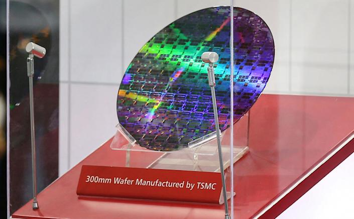 A reflective, circular semiconductor chip on display with a sign that says 300mm Wafer Manufactured by TSMC