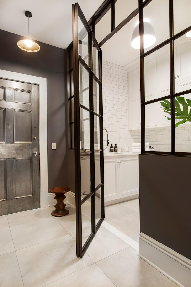 """The laundry room, which is near the back entrance of the apartment, shows Grehl's interpretation of Frank Lloyd Wright's """"compression and release"""" concept, where dark or narrow central areas lead to larger and brighter areas."""