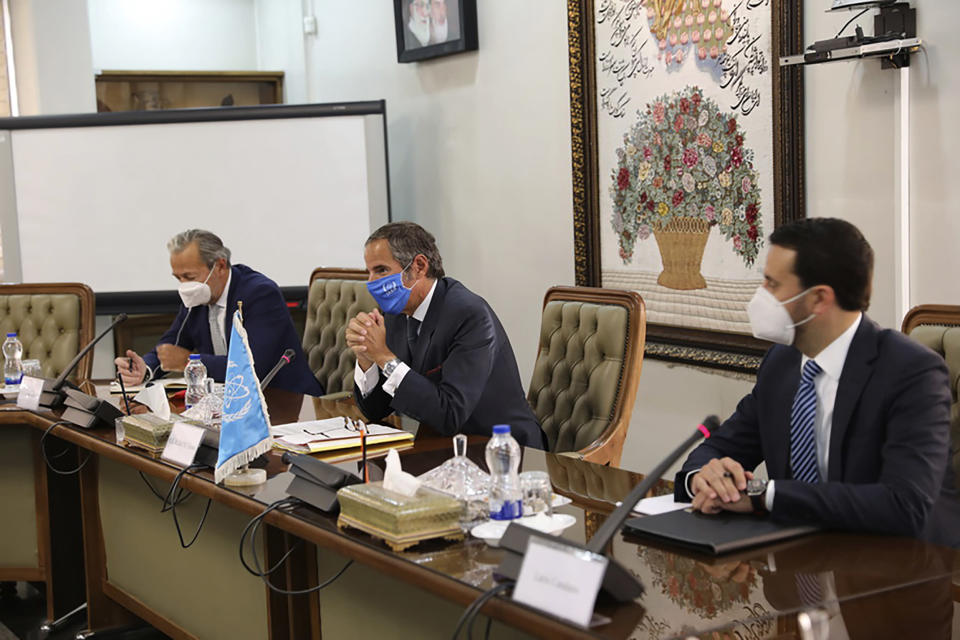 Rafael Mariano Grossi, Director General of International Atomic Energy Agency, IAEA, center, attends a meeting with the Head of Atomic Energy Organization of Iran, Mohammad Eslami, in Tehran, Iran, Sunday, Sept. 12, 2021. Iran agreed Sunday to allow international inspectors to install new memory cards into surveillance cameras at its sensitive nuclear sites and to continue filming there, averting a diplomatic showdown this week. (Atomic Energy Organization of Iran via AP)