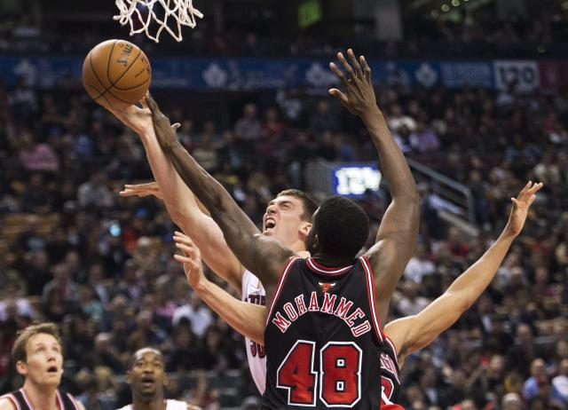 Toronto Raptors forward Tyler Hansbrough, back, drives to the net against Chicago Bulls forward Nazr Mohammed (48) during first-half NBA basketball game action in Toronto, Friday, Nov. 15, 2013. (AP Photo/The Canadian Press, Nathan Denette)