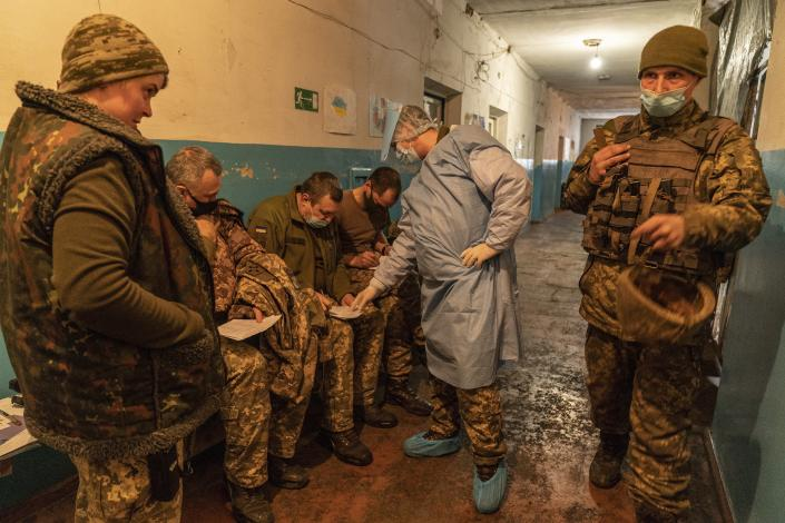 A Ukrainian military medic helps Ukrainian servicemen to fill in a medical form before receiving a dose of the AstraZeneca COVID-19 vaccine marketed under the name CoviShield at a military base near the front-line town of Krasnohorivka, eastern Ukraine, Friday, March 5, 2021. The country designated 14,000 doses of its first vaccine shipment for the military, especially those fighting Russia-backed separatists in the east. But only 1,030 troops have been vaccinated thus far. In the front-line town of Krasnohorivka, soldiers widely refuse to vaccinate. (AP Photo/Evgeniy Maloletka)