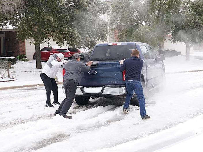 <p>Residents help a pickup driver get out of ice on the road in Round Rock, Texas, on 17 February, 2021, after a winter storm</p> (AFP via Getty Images)