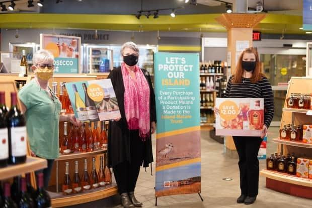 Helena Villard, PEILCC store manager, Darlene Compton, minister responsible for the PEILCC, and Bianca MacGregor, executive director of the Island Nature Trust, announce the return of the Let's Protect Our Island campaign. (Government of P.E.I. - image credit)