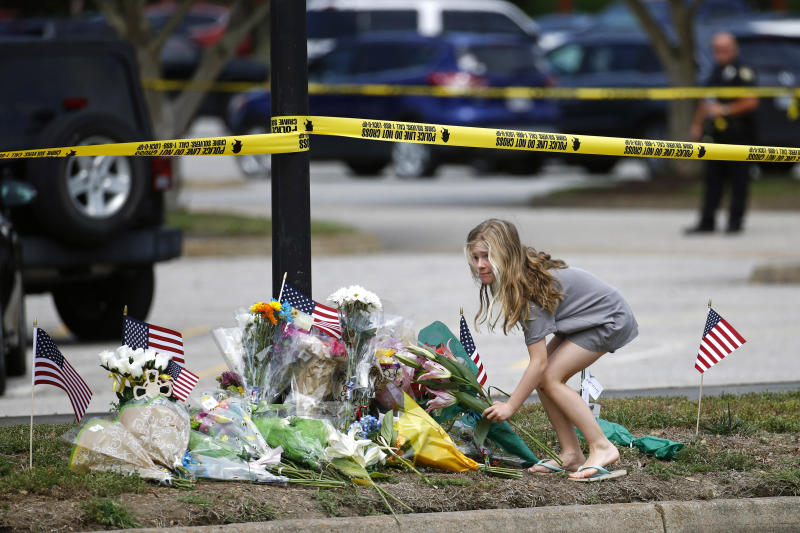 FILE - In this Saturday, June 1, 2019, file photo, a girl leaves flowers at a makeshift memorial at the edge of a police cordon in front of a municipal building that was the scene of a shooting, in Virginia Beach, Va. On Tuesday, Sept. 24, 2019, police are expected to release the findings of their investigation into the May 31 fatal mass shooting. (AP Photo/Patrick Semansky, File)