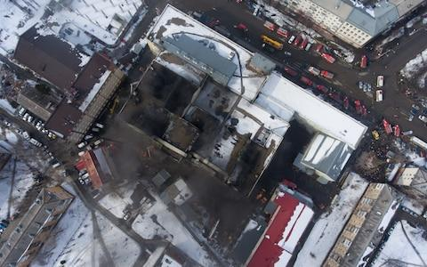 A view of the smoldering shopping centre from above on Monday morning - Credit: Kirill Kukhmar/TASS