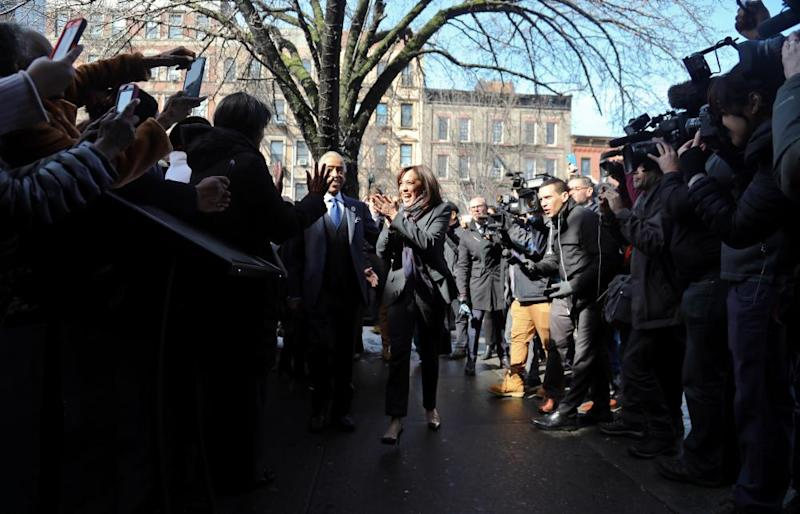 Civil rights leader Rev. Al Sharpton escorts Kamala Harris, D-Calif., center, past media and well wishers as they arrive for a lunch meeting at Sylvia's Restaurant in the Harlem neighborhood of New York in February 2019.