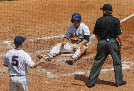 Mississippi's Nick Fortes (7) sits on home plate after being called out on a tag from Georgia catcher Austin Biggar (8) as Mississippi coach Mike Bianco (5) challenges the call during the fifth inning of a Southeastern Conference Tournament NCAA college baseball game, Thursday, May 24, 2018, in Hoover, Ala. (AP Photo/Butch Dill)
