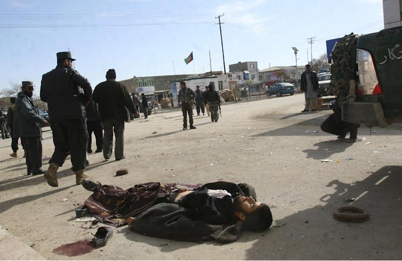 Security officers walk past a victim of a roadside bomb in Gazni, Afghanistan, Saturday, Jan. 26, 2013. A remote controlled bomb planted on a bicycle killed several people including a police officer and a civilian in the eastern city of Ghazni and Gen. Zirawer Zahid, the provincial police chief, says another five people were wounded.  (AP Photo/Rahmatullah Nikzad)