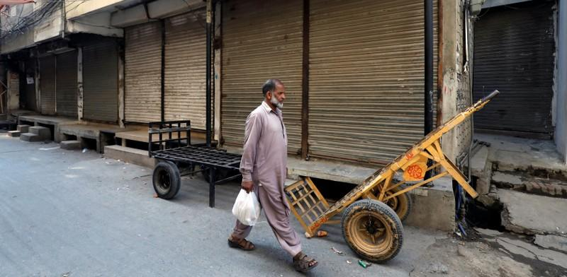 A man walks past closed shops during a country-wide lock down by the traders and business community against, what they say is imposition of taxes by the government in Rawalpindi