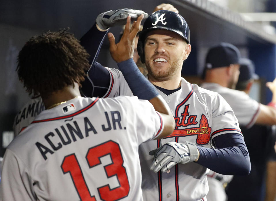 Atlanta Braves' Freddie Freeman, rear, is congratulated by Ronald Acuna Jr. (13) after Freeman hit a home run scoring Dansby Swanson during the first inning of a baseball game against the Miami Marlins, Friday, June 7, 2019, in Miami. (AP Photo/Wilfredo Lee)