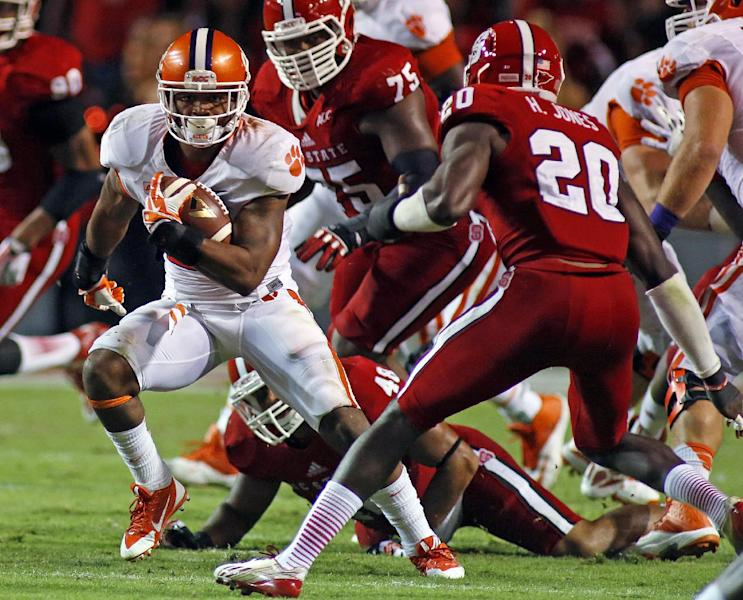 Clemson's Roderick McDowell (25) tries to avoid the tackle of North Carolina State's Hakim Jones (20) during the second half of an NCAA college football game in Raleigh, N.C., Thursday, Sept. 19, 2013. McDowell had 68 yards rushing in Clemson's 26-14 win. (AP Photo/Karl B DeBlaker)