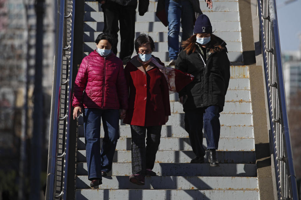 People wearing face masks to help curb the spread of the coronavirus walk down a pedestrian overhead bridge in Beijing, Sunday, March 21, 2021. (AP Photo/Andy Wong)
