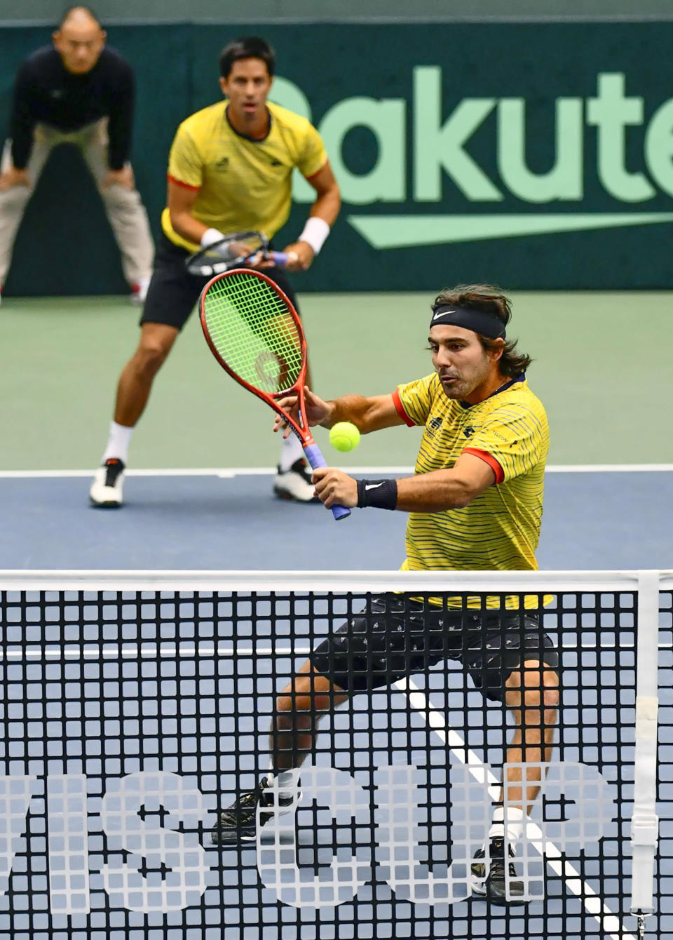 Ecuador's Diego Hidalgo, front, makes a return as his compatriot Gonzalo Escobar looks on in their double match against Japan's Ben McLachlan and Yasutaka Uchiyama during their Davis Cup qualifier in Miki, Hyogo prefecture, western Japan, Saturday, March 7, 2020. With no fans in the stands to give host Japan a boost, Ecuador took an insurmountable 3-0 lead on Saturday to secure a place in November's Davis Cup Finals in Madrid.(Nobuki Ito/Kyodo News via AP)