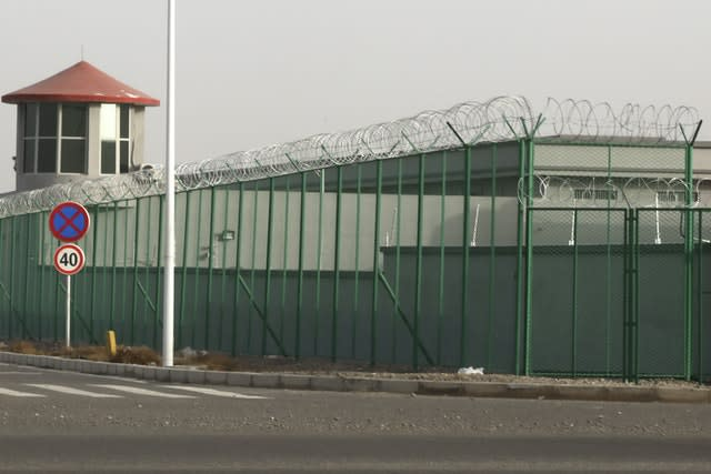 A guard tower and barbed wire fence surround a detention facility in the Kunshan Industrial Park in Artux in western China's Xinjiang region (Ng Han Guan/AP)