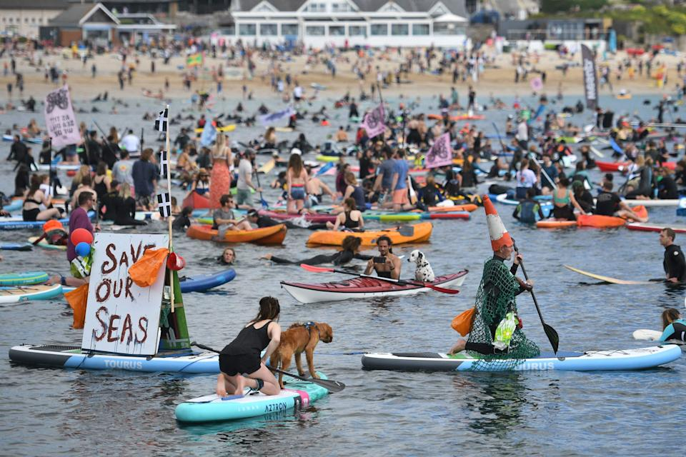 Surfers, paddleboarders and kayakers take part in an environmental protest in the water off Gyllyngvase beach in Falmouth, Cornwall during the G7 summit.