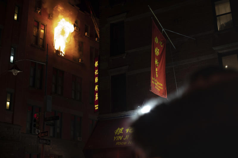Fire blows out of a window in the Chinatown section of New York, Thursday, Jan. 23, 2020. New York City firefighters battled a raging blaze at a building in the city's Chinatown area Thursday night, Firefighters said they were called about 8:45 p.m. to 70 Mulberry Street for a fire on the fourth and fifth floors of the building, NYFD officials said. (AP Photo/Robert Bumsted)