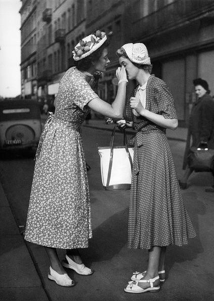 <p>Printed wrap dresses accessorized with embellished hats and white sandals dominate the summer street style scene in 1951. </p>