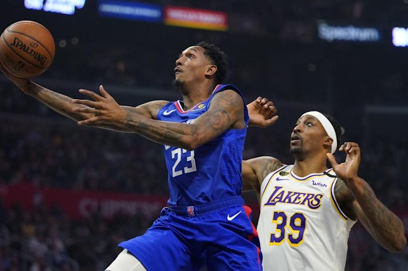 Los Angeles Clippers guard Lou Williams, left, shoots in front of Lakers center Dwight Howard.