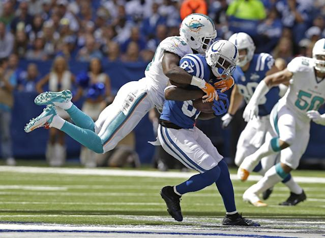 Indianapolis Colts' Reggie Wayne (87) is tackled by Miami Dolphins' Reshad Jones (20) during the first half an NFL football game Sunday, Sept. 15, 2013, in Indianapolis. (AP Photo/Michael Conroy)