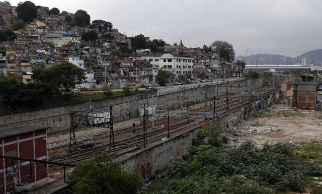 """The Metro Mangueira slum (R), which will be demolished for the 2014 World Cup infrastructure, is seen next to the Mangueira slum (L) and near the Maracana stadium in Rio de Janeiro March 25, 2014. According to a document released by the popular movement """"Comite Popular da Copa e Olimpiadas do Rio de Janeiro"""" (People's Committee of the World Cup and Olympic Games in Rio de Janeiro), the preparations for the 2014 World Cup and the 2016 Olympic Games in Rio de Janeiro will displace more than 7,185 families from their homes to make way for new sports facilities, bus routes for traffic and improvements in tourism infrastructure. REUTERS/Sergio Moraes (BRAZIL - Tags: SOCIETY SPORT SOCCER)"""