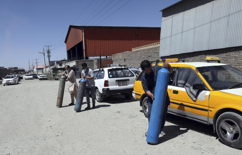 Men carry cylinders to be refilled from a privately owned oxygen factory, in Kabul, Afghanistan, Saturday, June 19, 2021. Health officials say Afghanistan is fast running out of oxygen as a deadly third surge of COVID worsen. (AP Photo/Rahmat Gul)