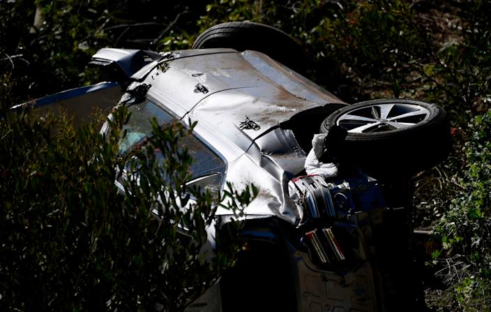 <p>The vehicle driven by golfer Tiger Woods lies on its side in Rancho Palos Verdes, California, on February 23, 2021, after a rollover accident</p> (Photo by PATRICK T. FALLON/AFP via Getty Images)
