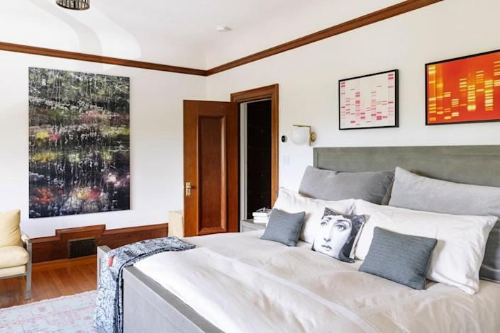 In the primary bedroom, DNA prints by DNA11 hang over the bed while Corner Deli Flowers, one of Chakrabarti's photographs, hangs on the adjacent wall. A Fornasetti pillow can also be seen.