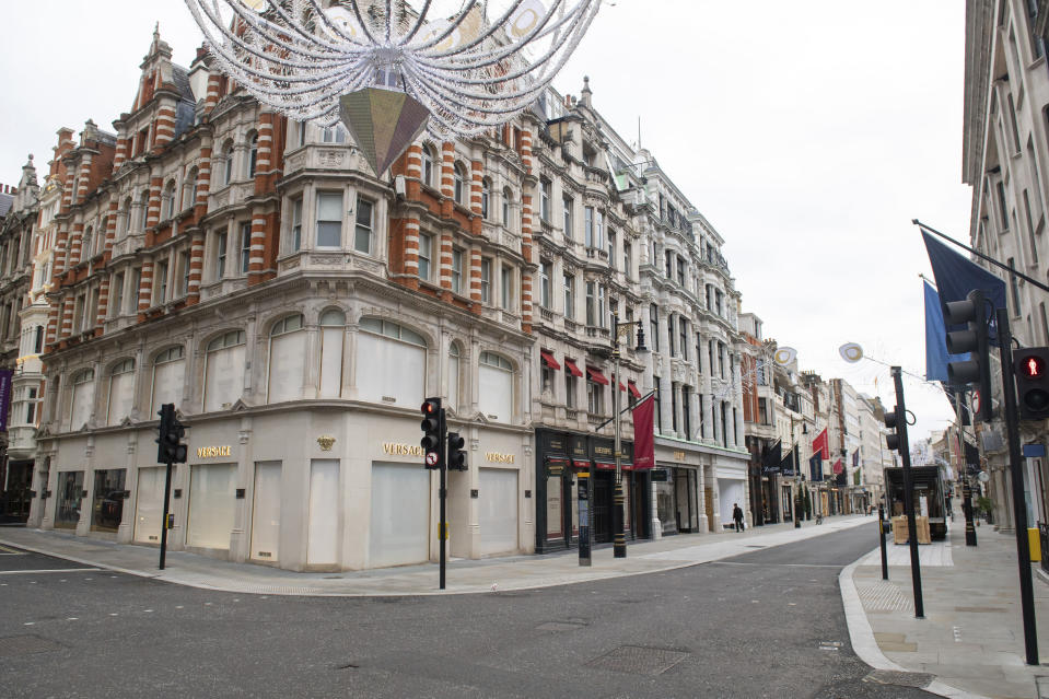 A general view of closed shops on an empty New Bond Street, as England continues a four week national lockdown to curb the spread of coronavirus, in London, Tuesday, Nov. 17, 2020. (Dominic Lipinski/PA via AP)