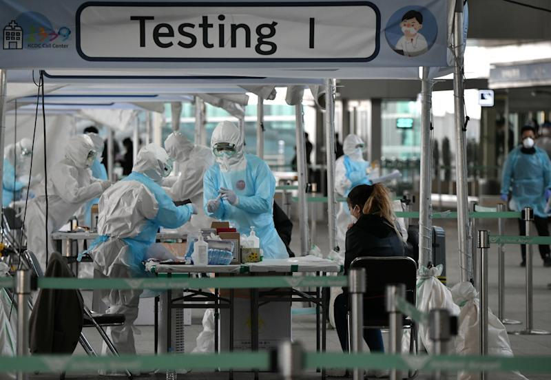 TOPSHOT - Medical staff wearing protective clothing take test samples for the COVID-19 coronavirus from a foreign passenger at a virus testing booth outside Incheon international airport, west of Seoul, on April 1, 2020. - The first charter flight arranged by South Korean government to evacuate its citizens from coronavirus-hit Italy returned home with 309 citizens on April 1, amid the worsening virus outbreak in the European country. (Photo by Jung Yeon-je / AFP) (Photo by JUNG YEON-JE/AFP via Getty Images)