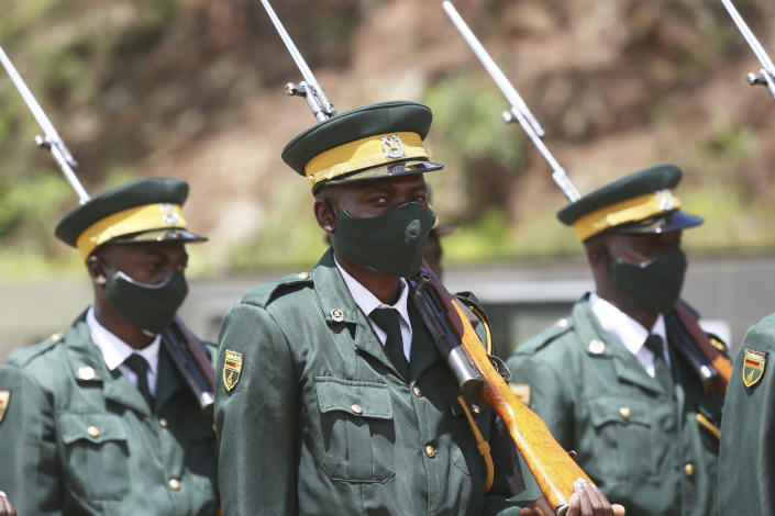 """Soldiers stand guard while attending a state burial of government ministers who died of COVID-19, in Harare, Thursday, Jan. 21, 2021. Zimbabwean President Emmerson Mnangagwa who presided over the burial called the pandemic """"evil"""" and urged people to wear masks, practice social distancing and sanitize, as cases across the country increased amid a fragile health system. (AP Photo/Tsvangirayi Mukwazhi)"""