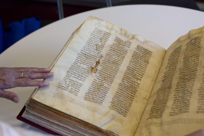 """FILE - In this Oct. 5, 2014 file photo, a library official shows a Jewish manuscript smuggled into Israel from Damascus in a Mossad spy operation in the early 1990s, in Jerusalem. The manuscript is one of the earliest existing complete manuscripts of the Hebrew bible. The Jerusalem District Court ruled Monday, Aug. 17, 2020 that the books were """"treasures of the Jewish people"""" that had """"historic, religious and national importance"""" and must be preserved. It determined that the best way to do so would be to keep them at the National Library under a public trust. (AP Photo/Sebastian Scheiner, File)"""