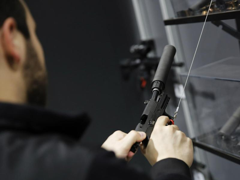 A visitors pulls the slide of a pistol with a silencer at a gun displays at a National Rifle Association outdoor sports trade show on 10 February 2017 in Harrisburg, Pennsylvania: DOMINICK REUTER/AFP/Getty Images