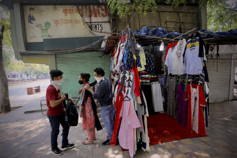 People shop for clothes at the Janpath market in New Delhi, India, Monday, June 1, 2020. More states opened up and crowds of commuters trickled onto the roads in many of India's cities on Monday as a three-phase plan to lift the nationwide coronavirus lockdown started despite an upward trend in new infections. (AP Photo/Manish Swarup)