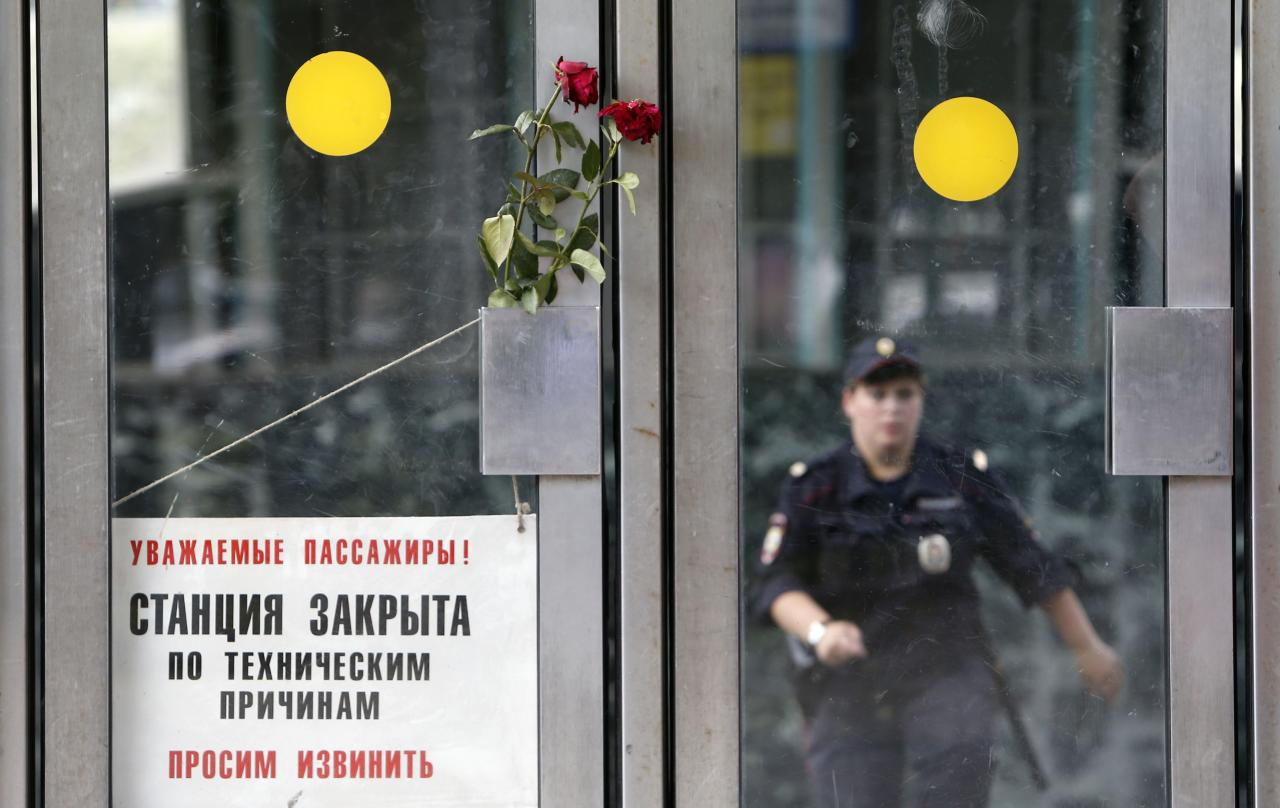 Flowers in memory of victims of Tuesday's accident, in which three carriages derailed on a train during morning rush hour, are left next to a sign informing passengers that the station is closed due to technical reasons, at the entrance to a metro station in Moscow July 16, 2014. Russian state investigators said on Wednesday they had detained two Moscow metro workers suspected of safety breaches that may have caused an accident that killed at least 21 people. REUTERS/Sergei Karpukhin (RUSSIA - Tags: TRANSPORT DISASTER)