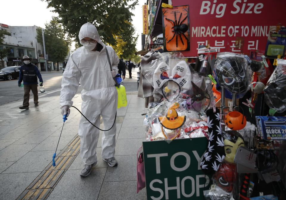 A man wearing protective gear disinfects on a street as a precaution against the coronavirus in Seoul, South Korea, Thursday, Oct. 29, 2020. (AP Photo/Lee Jin-man)