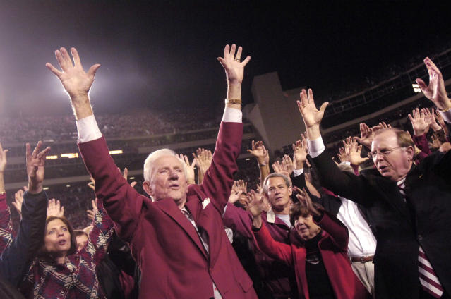 FILE - In this Nov. 3, 2007, file photo, former Arkansas coach and athletic director Frank Broyles, left, and school Chancellor John White, right, lead the school's cheer on the field at Reynolds Razorback Stadium during halftime ceremonies in a NCAAA college football game against South Carolina in Fayetteville, Ark. Broyles was retiring at the end of that year, his 50th with the school. (AP Photo/Beth Hall, File)