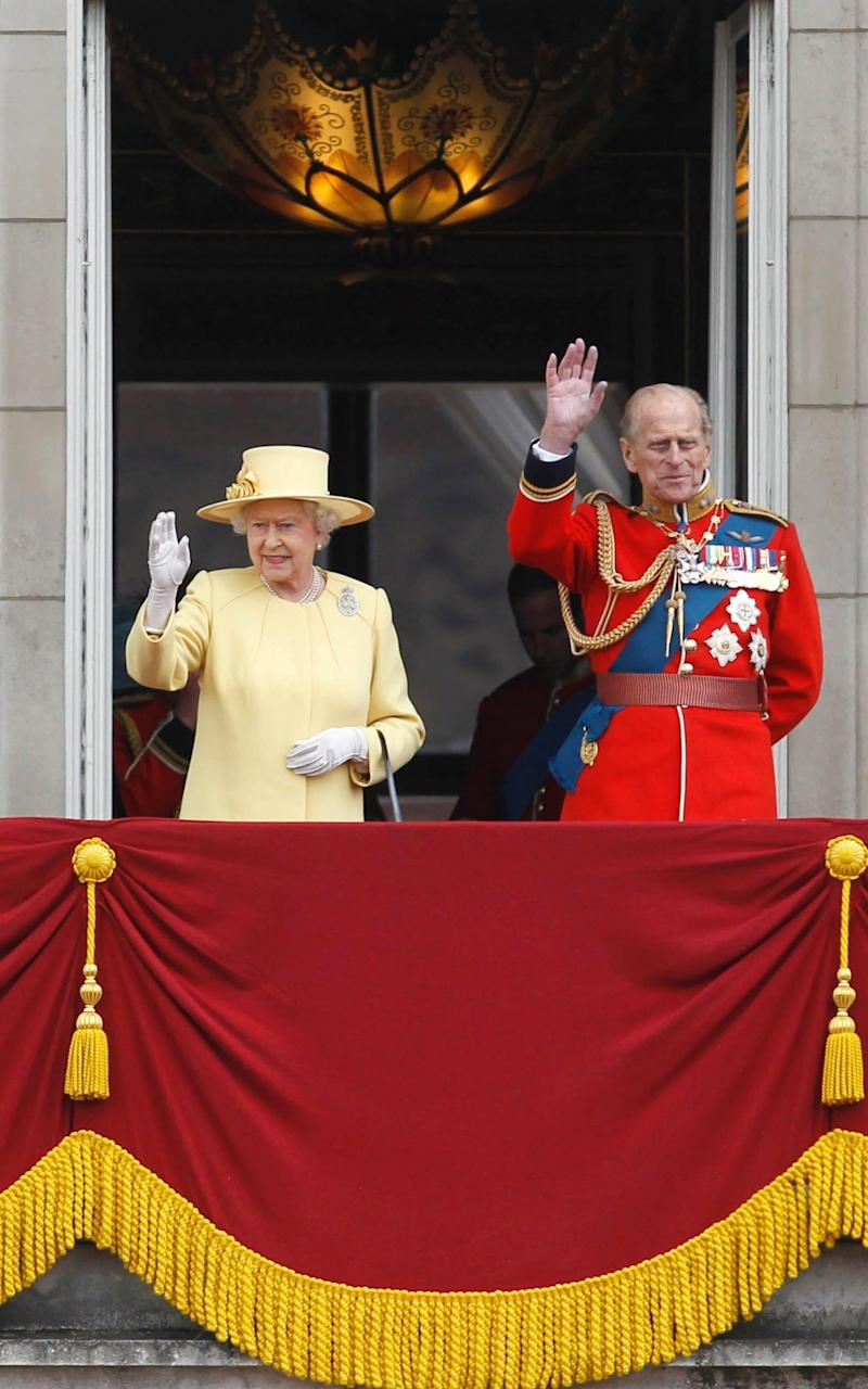 Queen Elizabeth II and Prince Philip wave from the balcony of Buckingham Palace - Credit: AP Photo/Sang Tan