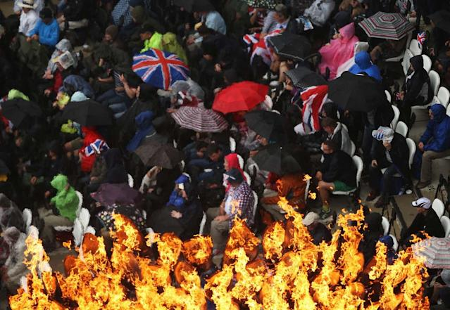 LONDON, ENGLAND - AUGUST 03: The Olympic Cauldron burns as spectators shelter from the rain on Day 7 of the London 2012 Olympic Games at Olympic Stadium on August 3, 2012 in London, England. (Photo by Ian Walton/Getty Images)