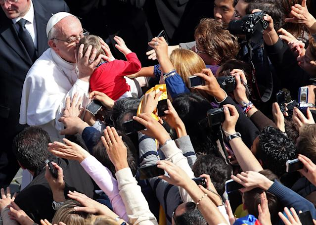 VATICAN CITY, VATICAN - MARCH 24: Pope Francis kisses a child as he greets the faithful after conducting Palm Sunday Mass on March 24, 2013 in Vatican City, Vatican. Pope Francis lead his first mass of Holy Week as pontiff by celebrating Palm Sunday in front of thousands of faithful and clergy. The pope's first holy week will also incorporate him washing the feet of prisoners in a youth detention centre in Rome next Thursday, 28th March. (Photo by Christopher Furlong/Getty Images)