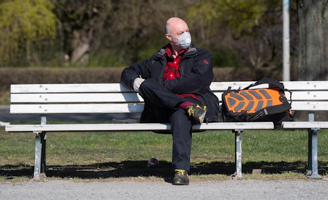 A man is sitting while wearing a mask at the Maschsee lake near Hanover on 25 March. Germany has had more than 33,500 confirmed cases. (Getty Images)