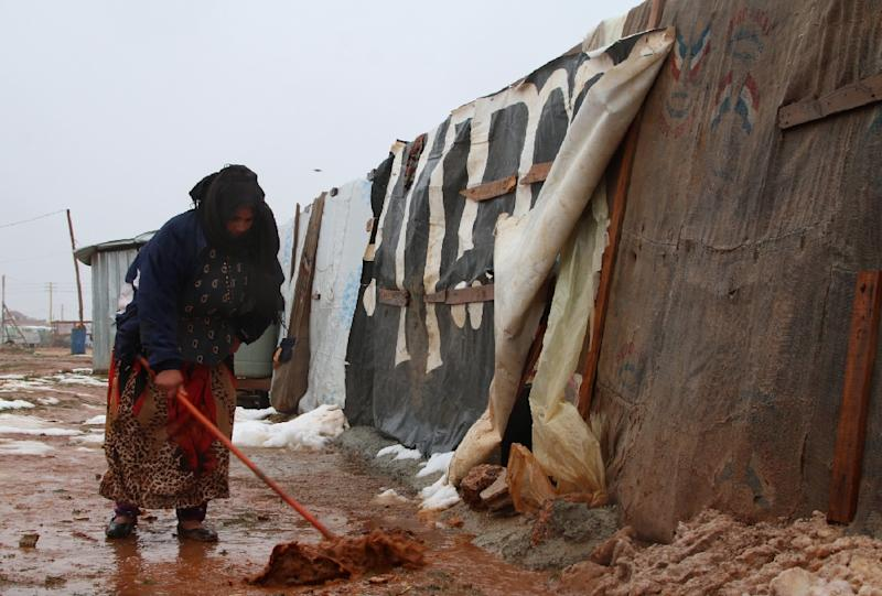 A Syrian refugee shovels mud in front of a makeshift shelter in an unofficial refugee camp in Lebanon after it was lashed by severe weather on January 8, 2019 (AFP Photo/-)