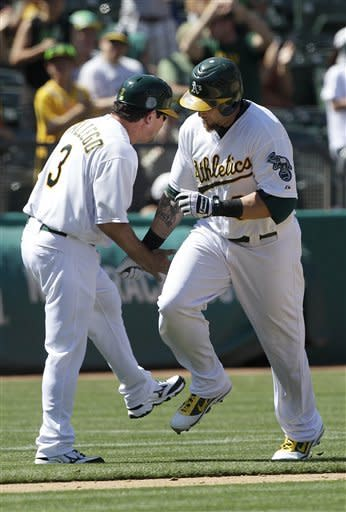 Oakland Athletics' Jonny Gomes, right, celebrates with third base coach Mike Gallego (3) after hitting a two-run home run off of San Diego Padres pitcher Luke Gregerson during the seventh inning of a baseball game in Oakland, Calif., Saturday, June 16, 2012. The Athletics won 6-4. (AP Photo/Jeff Chiu)