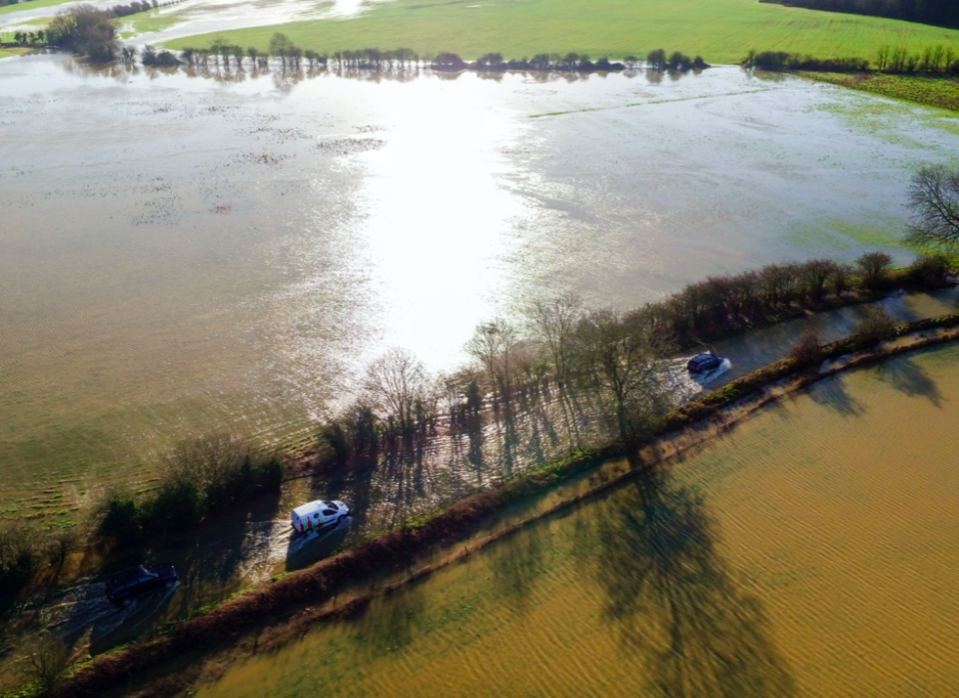 Vehicles negotiate the flooded B4069 road at Christian Malford in Wiltshire after the river Avon burst its banks (PA)
