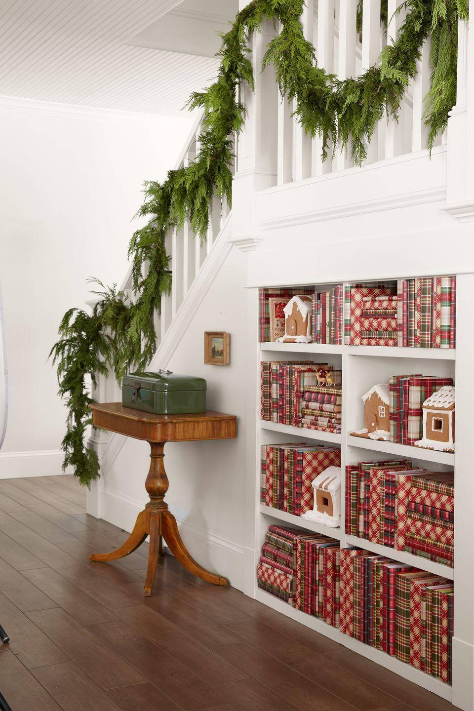 """<p>Easy-to-overlook bookcases get a graphic jolt by covering hardbacks with affordable plaid gift wrap.</p><p><a class=""""link rapid-noclick-resp"""" href=""""https://www.amazon.com/s/ref=nb_sb_noss?url=search-alias%3Dgarden&field-keywords=christmas+garland&tag=syn-yahoo-20&ascsubtag=%5Bartid%7C10050.g.1247%5Bsrc%7Cyahoo-us"""" rel=""""nofollow noopener"""" target=""""_blank"""" data-ylk=""""slk:SHOP GARLAND"""">SHOP GARLAND</a> </p>"""