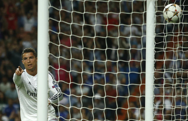 <p>Real Madrid's Cristiano Ronaldo scores his side's third goal during the Champions League Group B soccer match between Real Madrid and Basel at the Santiago Bernabéu Stadium in Madrid, Sept. 16, 2014. (AP Photo/Andres Kudacki) </p>