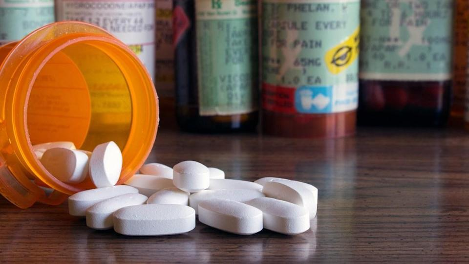 White prescription pills spilled onto a table with many prescription bottles in the background