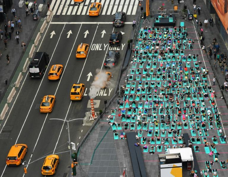 People take part in the 15th annual Times Square yoga event celebrating the Summer Solstice, the longest day of the year, and the international day of yoga during classes in the middle of Times Square (AFP Photo/TIMOTHY A. CLARY)