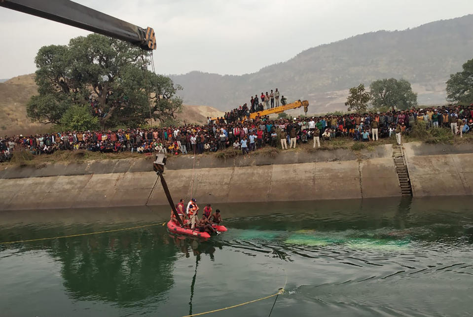 Rescuers work at the site of a bus accident in Sidhi district, in the central Indian state of Madhya Pradesh, Tuesday, Feb. 16, 2021. An official says an overcrowded bus has driven off a bridge and into a canal in central India, killing at least 40 people. (Madhya Pradesh District Public Relation Office Sidhi via AP)