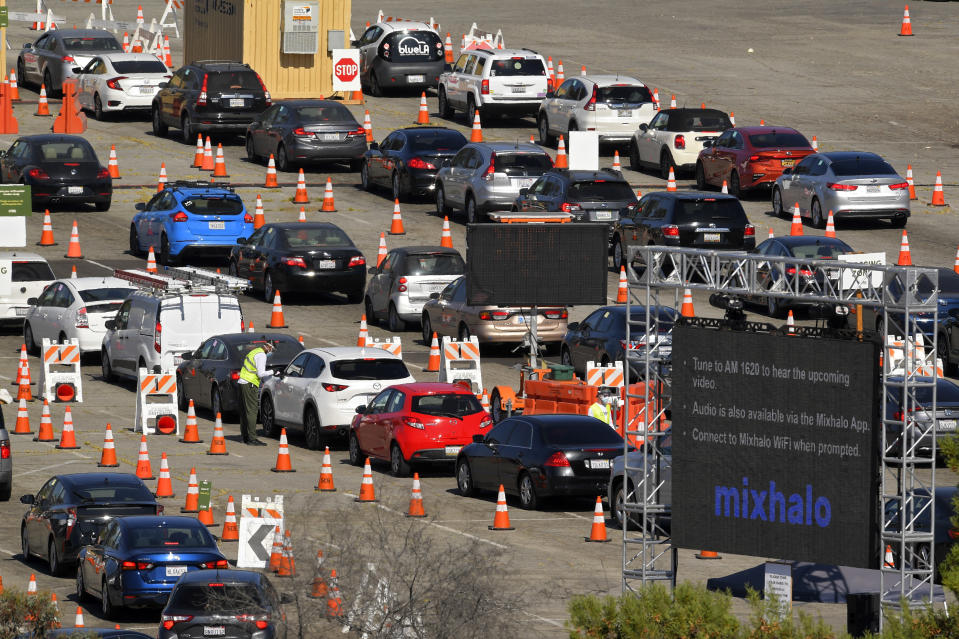 People wait in line for coronavirus testing at Dodger Stadium Tuesday, July 14, 2020, in Los Angeles. (AP Photo/Mark J. Terrill)